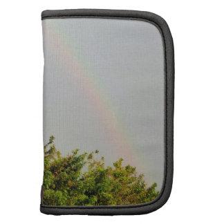Foto doble del arco iris con el cielo y los árbole organizadores