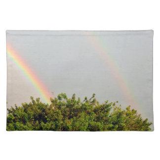 Foto doble del arco iris con el cielo y los árbole manteles individuales
