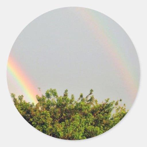 Foto doble del arco iris con el cielo y los árbole etiqueta redonda