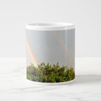Foto doble del arco iris con el cielo y los árbole tazas jumbo