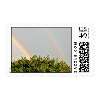 Foto doble del arco iris con el cielo y los estampillas