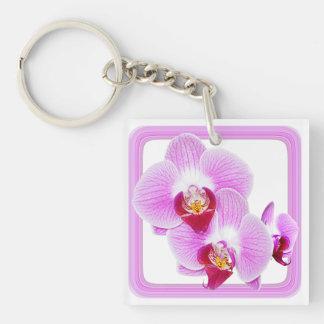 Foto radiante del primer de la orquídea con el mar llaveros