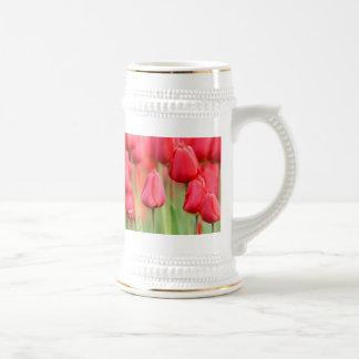 Foto roja de los tulipanes jarra de cerveza