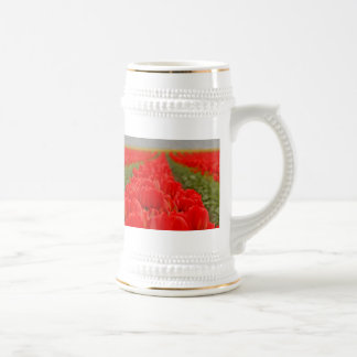 Foto roja del campo de los tulipanes jarra de cerveza
