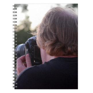 fotógrafo que toma a imagen la parte posterior de libro de apuntes con espiral