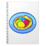 four colored eggs next blue oval.png spiral notebooks
