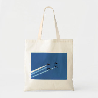 four flying planes with trails blue sky bag