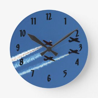 four flying planes with trails blue sky clock