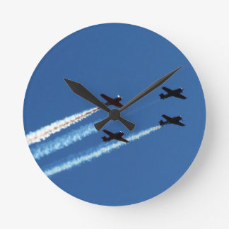 four flying planes with trails blue sky round wall clocks