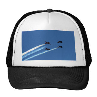 four flying planes with trails blue sky trucker hats