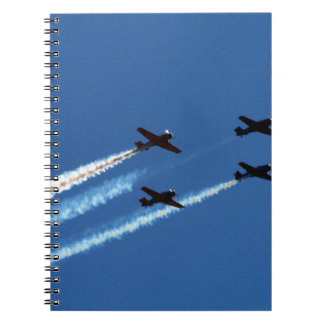 four flying planes with trails blue sky journals