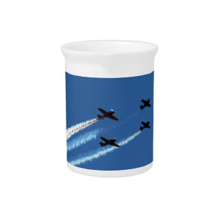 four flying planes with trails blue sky beverage pitchers