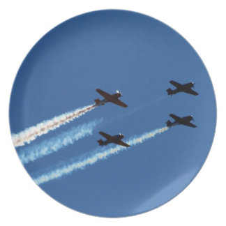 four flying planes with trails blue sky plates