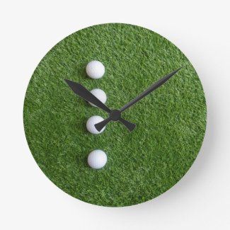 Four golf balls are on green grass round clock