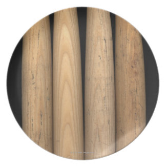 Four old baseball bats on black background melamine plate