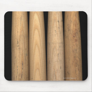 Four old baseball bats on black background mouse pad