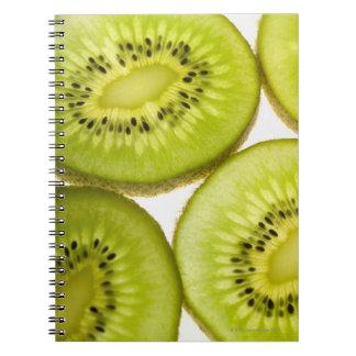 Four pieces of sliced kiwi notebooks