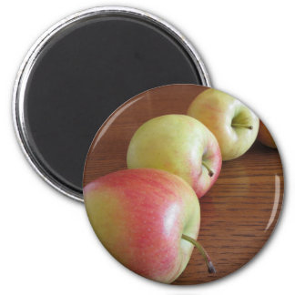 Four ripe apples on wooden table magnet