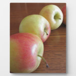 Four ripe apples on wooden table plaque