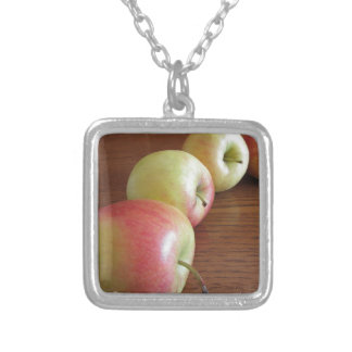 Four ripe apples on wooden table silver plated necklace