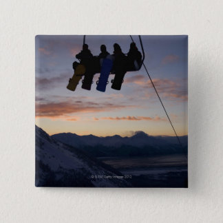 Four snowboarders are silhouetted on a ski lift button