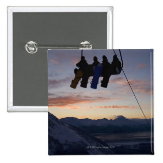 Four snowboarders are silhouetted on a ski lift pin