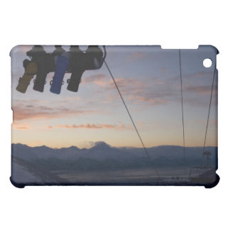 Four snowboarders are silhouetted on a ski lift cover for the iPad mini