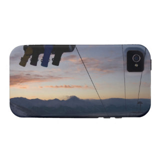 Four snowboarders are silhouetted on a ski lift iPhone 4 case