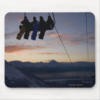Four snowboarders are silhouetted on a ski lift mouse pad