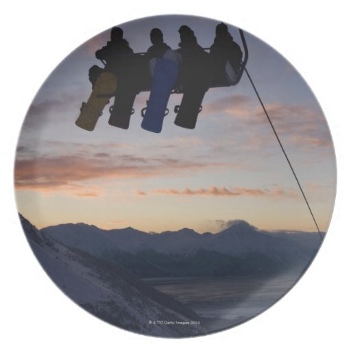 Four snowboarders are silhouetted on a ski lift party plate