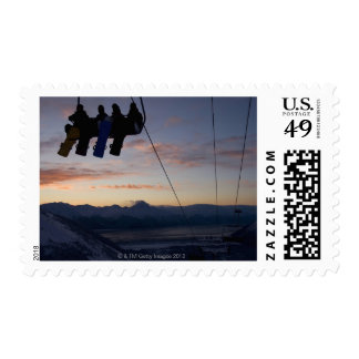 Four snowboarders are silhouetted on a ski lift stamp