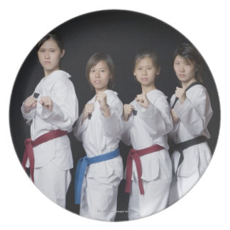 Four young women standing in punching position melamine plate