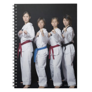 Four young women standing in punching position spiral notebook
