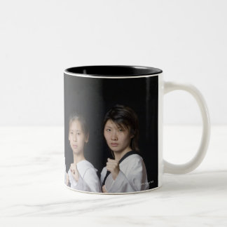 Four young women standing in punching position Two-Tone coffee mug