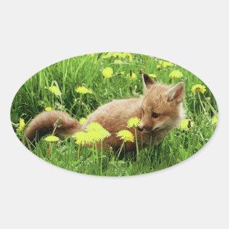 Fox rojo del bebé en campo verde con las flores pegatina ovalada