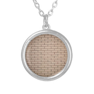 Fragment of a brick wall beige with neat rows of m round pendant necklace