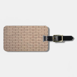 Fragment of a brick wall beige with neat rows of m travel bag tags