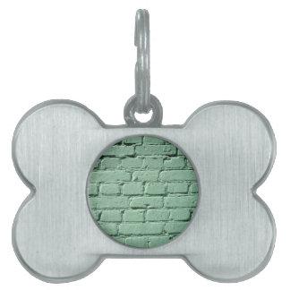 Fragment of a green brick wall pet ID tag