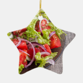 Fragment of a transparent plate with a fresh salad ceramic ornament