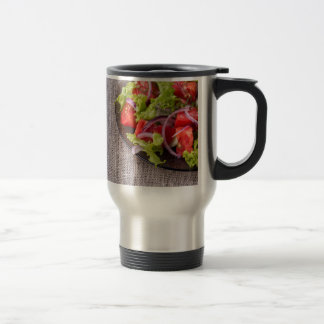 Fragment of a transparent plate with a fresh salad travel mug