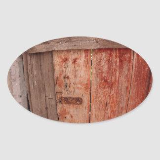 Fragment of an old wooden fence in the shade of th oval sticker