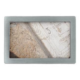 Fragment of ancient stone dial sundial closeup rectangular belt buckle