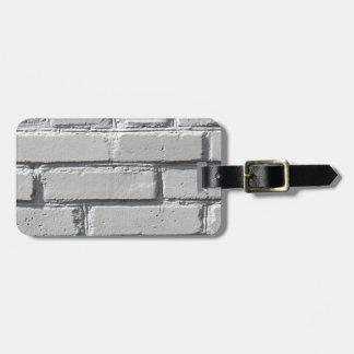 Fragment of gray brick wall closeup luggage tag