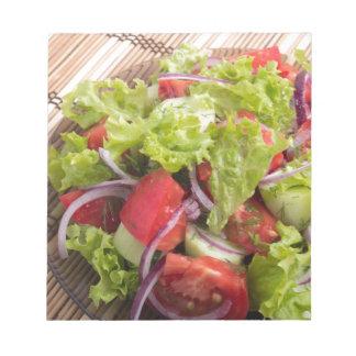 Fragment of vegetarian salad from fresh vegetables notepad