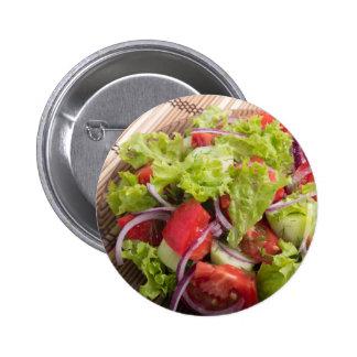 Fragment of vegetarian salad from fresh vegetables pinback button