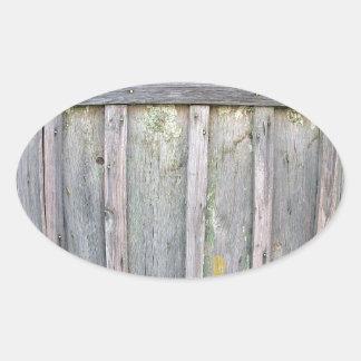 Fragmento de una cerca de madera vieja de tableros pegatina ovalada