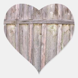Fragmento de una cerca de madera vieja de tableros pegatina en forma de corazón