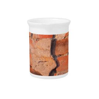 Fragmento de una pared de ladrillo lamentable jarras de beber