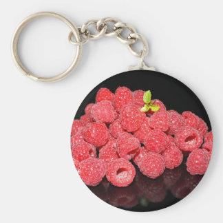 frambuesas rojas frescas reflejadas en backgroun llavero redondo tipo pin