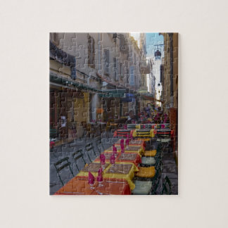 France, Corsica. Tables of cafe set up in narrow Jigsaw Puzzle